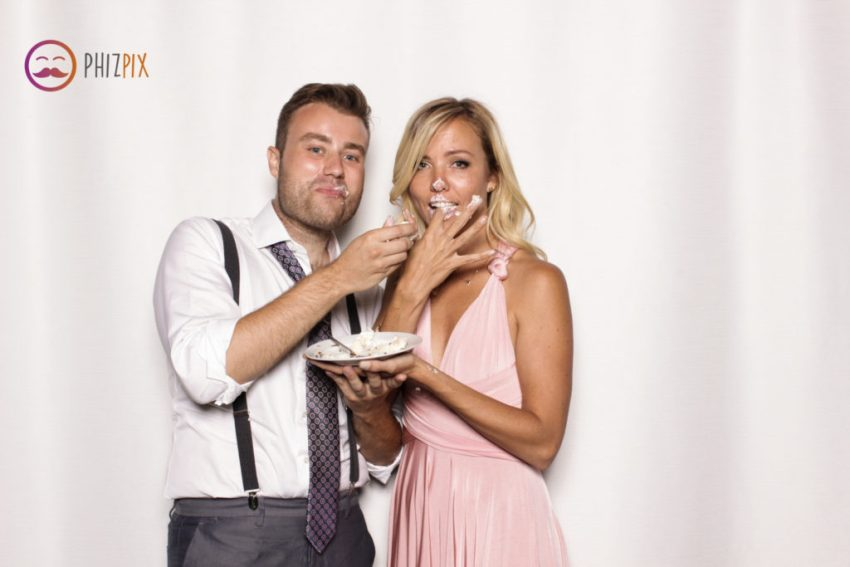 Two guests eating messy wedding cake in the Malibu photo booth