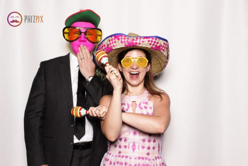 A girl having fun with a sombrero and maracas, next to a guy covering a smile with his hand while wearing a pink mask, a robin hood hat and huge sunglasses in the Malibu photo booth