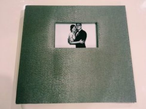 A picture of a guestbook containing a photo of the bride and groom on the cover