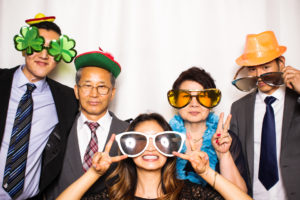 A family posing wearing props in the photo booth