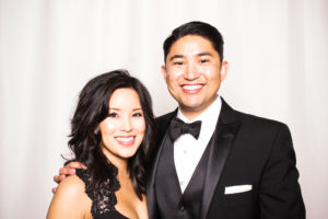 A couple smiling in the photo booth