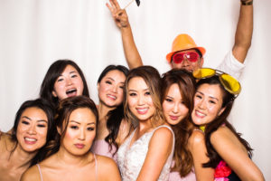 A bride and friends being photo bombed by a guy in an orange hat in the photo booth