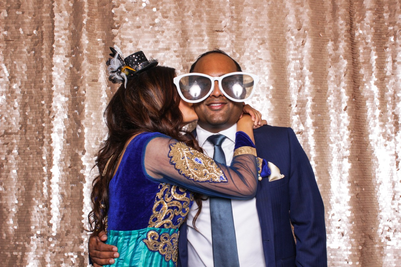 A guy wearing big glasses being kissed on the cheek in the pasadena photo booth