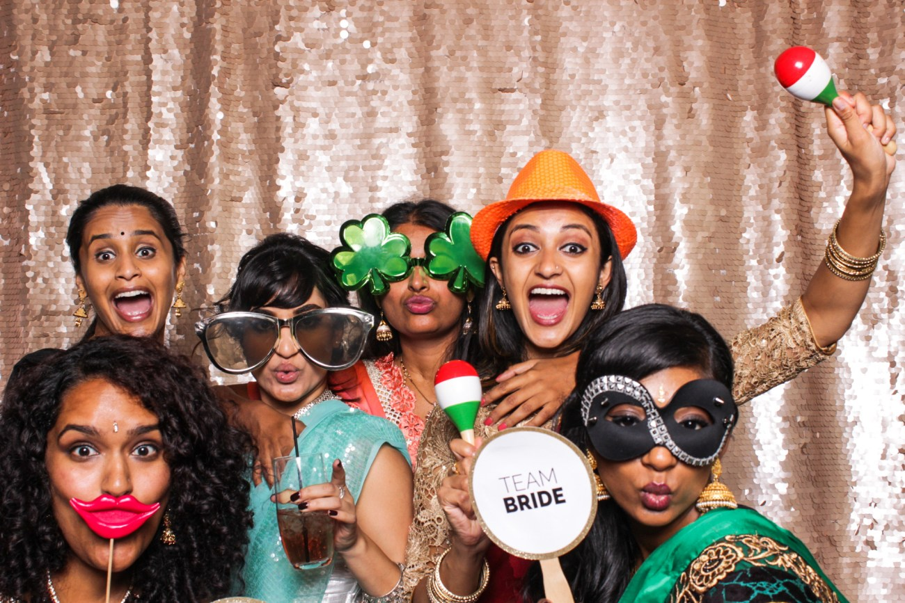 Wedding guests pulling funny faces and having fun with props in the pasadena photo booth