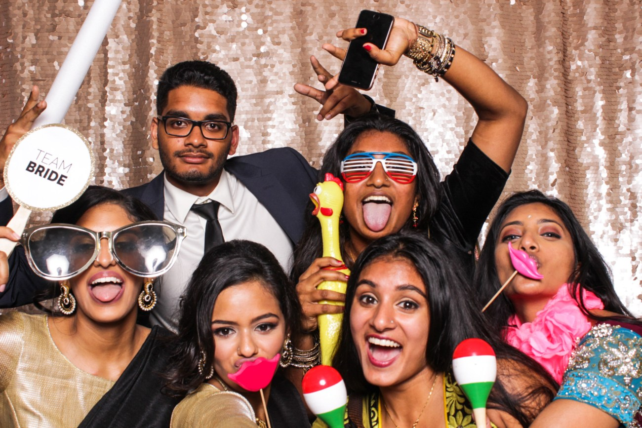 A group of friends having fun with maracas in the pasadena photo booth