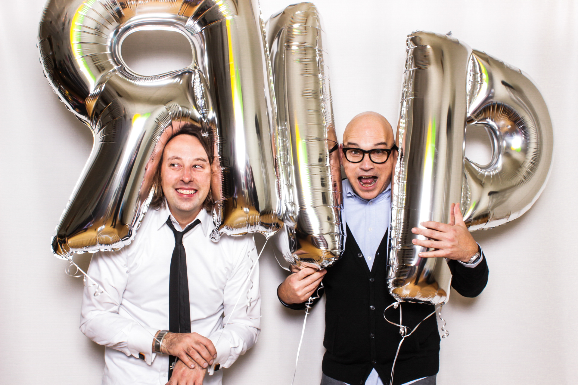 Two friends posing with big balloons in front of their Phizpix photo booth rental