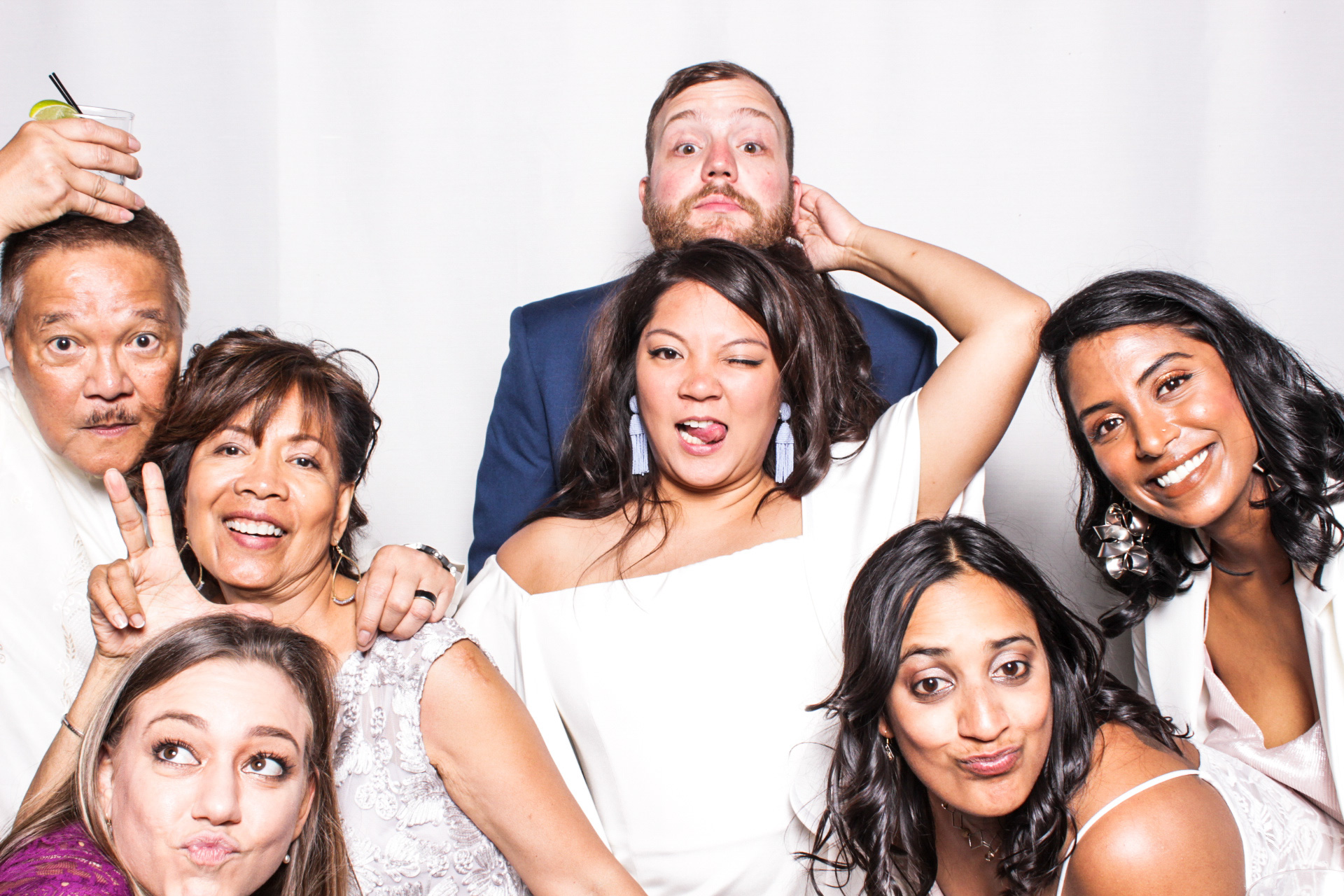 A bride and groom posing in front of their Phizpix photo booth rental with friends