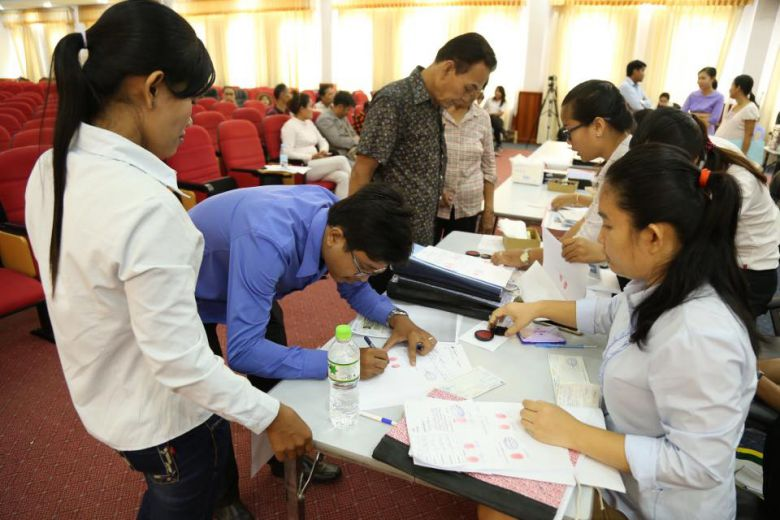 White Building residents sign contracts accepting compensation offered by the Land Ministry yesterday in Phnom Penh. Facebook