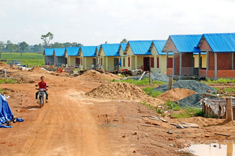 A man rides past houses under construction at a relocation site for villagers affected by the Lower Sesan II dam in Stung Treng province in 2015.