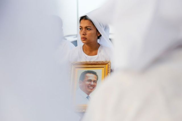 Bou Rachana, Kem Ley's wife, holds a portrait of her late husband as the funeral procession makes its way through Phnom Penh yesterday morning.