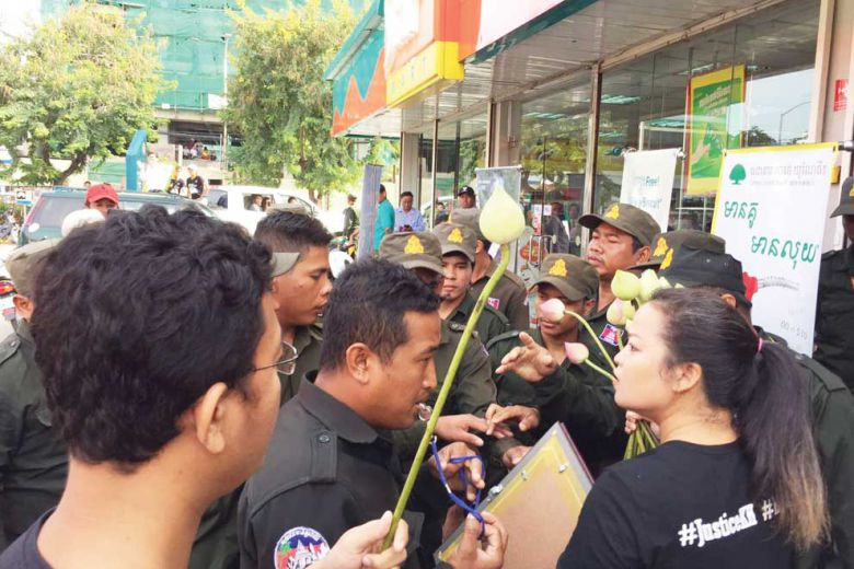 Supporters commemorating the first anniversary of the killing of political analyst Kem Ley speak to officials as they are blocked from entering the Star Mart where he was murdered. Licadho