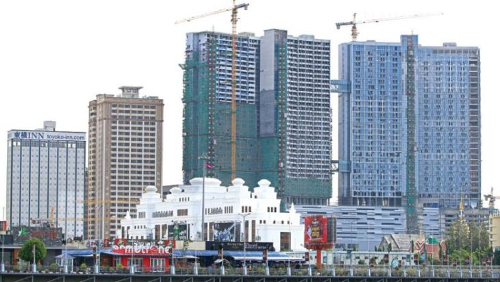 Cranes and green mesh cover The Bridge, a $300 million mixed-use project expected to open later this year, adding 762 condominium units to the capital's supply.