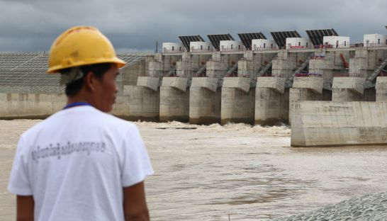 A worker stands in front of the Lower Sesan II Dam as it was put online yesterday in Stung Treng province. The controversial hydropower structure is expected to provide a boost to the Kingdom's electricity supply but is also expected to cause significant damage to fisheries.