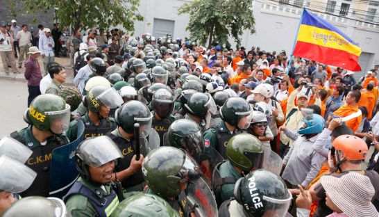 Buddhist monks and supporters face off against security personnel during a Khmer Krom protest in Phnom Penh
