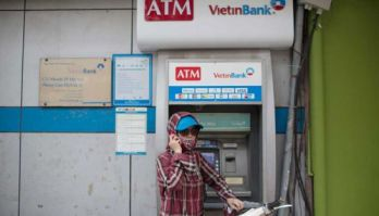 A woman holds a mobile phone in front of an ATM in Vietnam