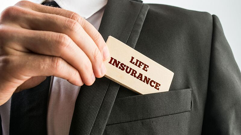 business man slipping life insurance card into his pocket