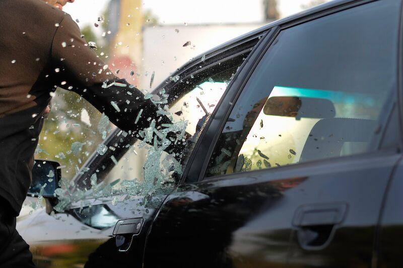 criminal breaking car window