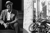 Life – man in hat and suit sits on stoop beside tricycles