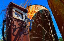 Conceptual – rusting gas pump oil tanks and stark tree