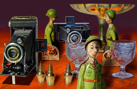 a photo-composited collage of an antique tin toy, camera, glass goblet, and silver tableware