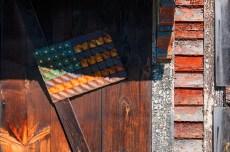 Conceptual – marijuana wood grain pattern and american flag on door of weathered clapboard house