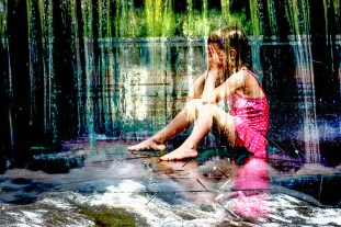 Life – A water soaked girl sits in a cascade of water