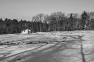 Black & White – tiny white cottage in winter field with tree shadows