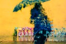 Conceptual – wet figure with umbrella walks toward supermarket with mustard colored wall