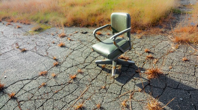 Conceptual – abandoned like a fart, a lonely office chair in parking lot