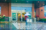 Abstract – wet figure with umbrella exiting grocery store in the rain