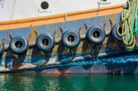 Graphic – chained tire bumpers on colorful fishing boat at dock.