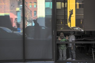 Life – boy peers at photographer from behind window reflecting city
