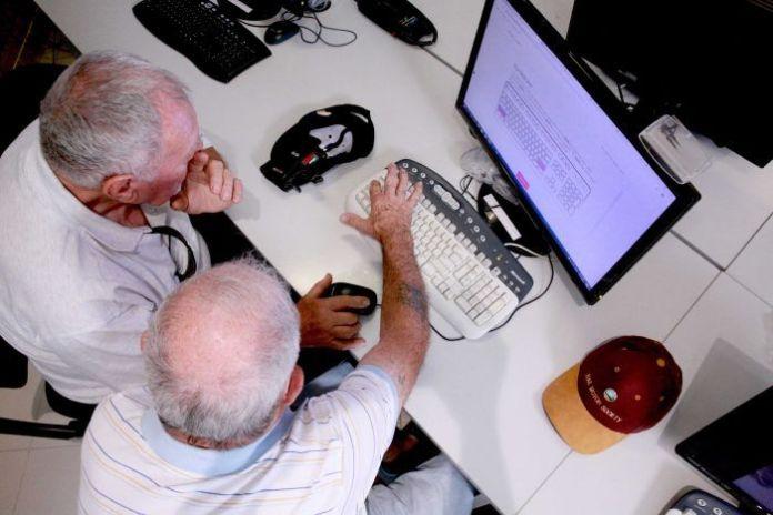 Two older men use a computer together.