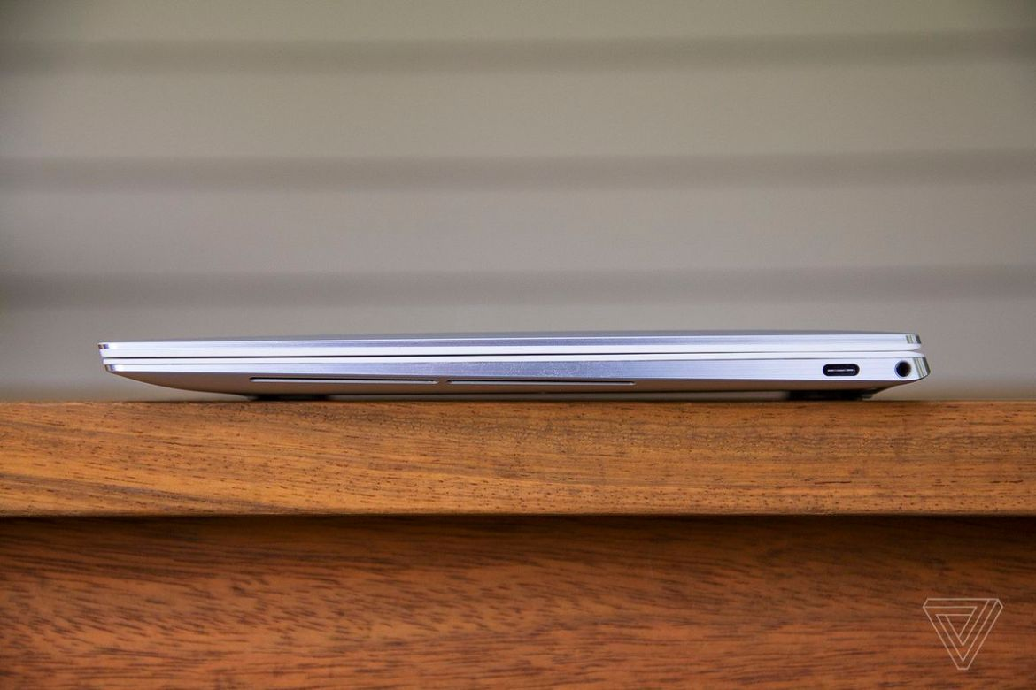 The Dell XPS 13 OLED closed seen from the left side on a wooden table.