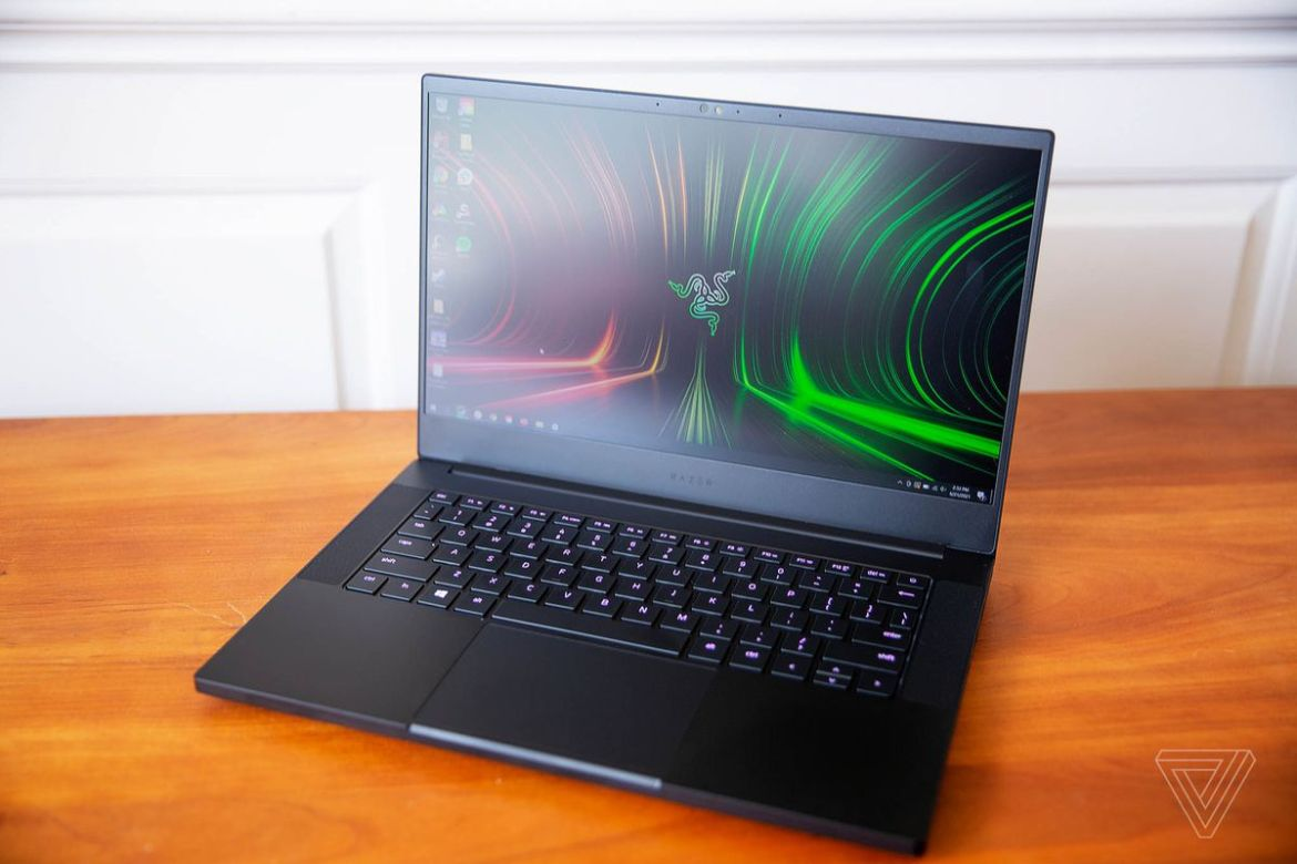 The Razer Blade 14 seen from above, open, angled to the left. The screen displays the Razer logo on a red and green background. The keys are lit a dark pink.