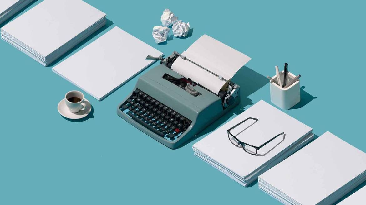 A blue typewriters on a turquoise blue background with paper, pens, and a coffee mug.