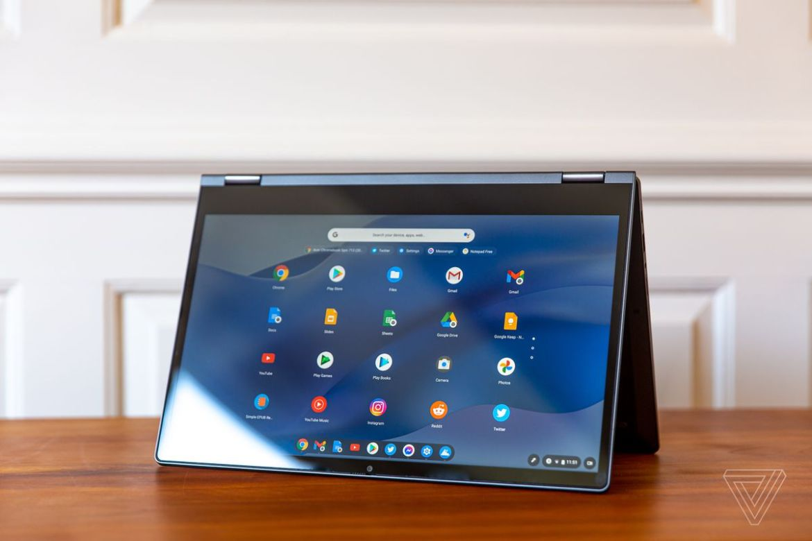 The Lenovo Flex 5 Chromebook in tent mode, angled to the left. The screen displays a grid of Chrome OS icons on a blue wavy background.