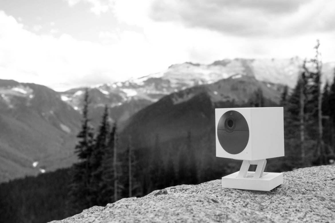 A black and white photo of a Wyze Cam Outdoor model in a mountainous area.