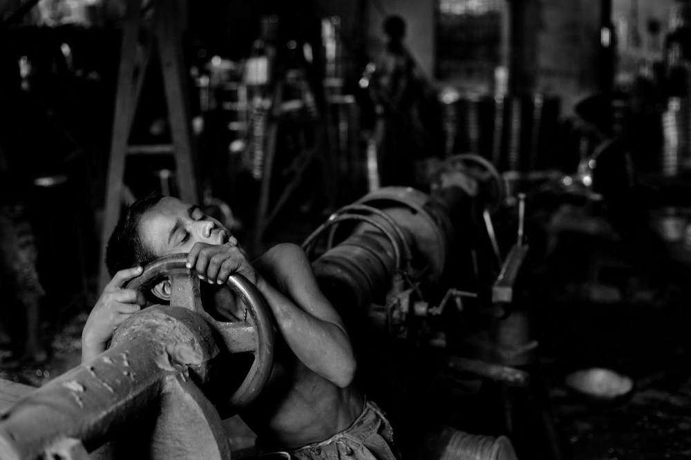 "© Md Shahnewaz Khan from the series ""Fallen Stars""; Shakil falls asleep on his tools after hard work at aluminum factory, Chittagong, Bangladesh, 2013"