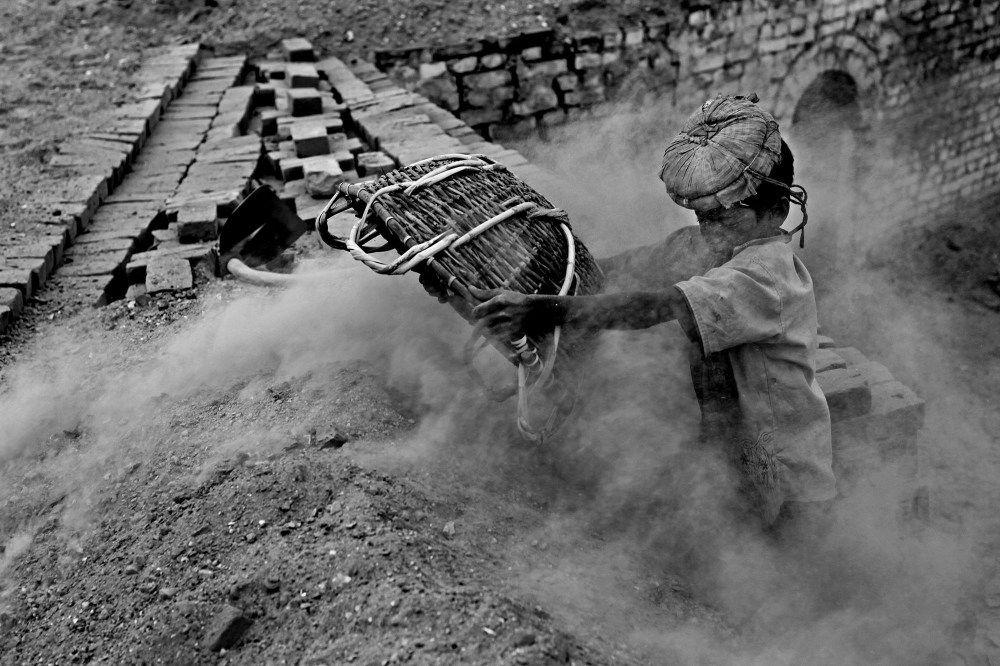 """© Md Shahnewaz Khan from the series """"Fallen Stars""""; Shafik (11) working above the pile of burning bricks in a brickfield. The work is extremely dangerous and vulnerable for children. Bakkar brickfield in Chittagong, Bangladesh, 2013"""