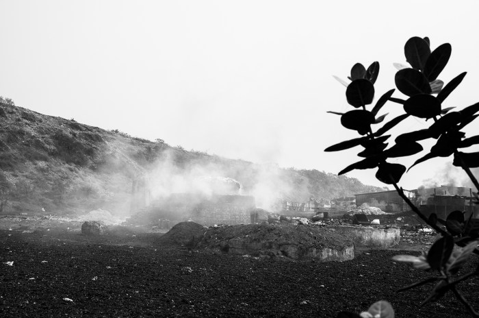 """© Debmalya Ray Choudhuri from the series """"Life in the Wasteland"""" - The brick field furnaces in operation .The scrap ,leather and cloth and some products which cannot be recycled are burnt in large open furnaces like these. They generate huge amount of toxic gases and people here are exposed to them .They believe it is not so harmful to work and keep on going."""