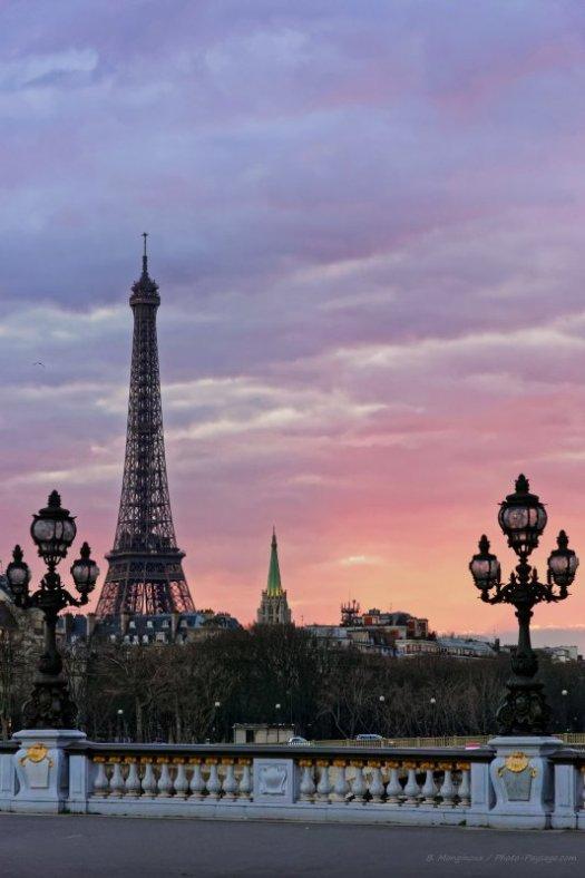 Un beau ciel nuageux teinté de rose et de mauve en fin de journée à Paris. Photo prise depuis le pont Alexandre III. En arrière plan : la Tour Eiffel en contre-jour.