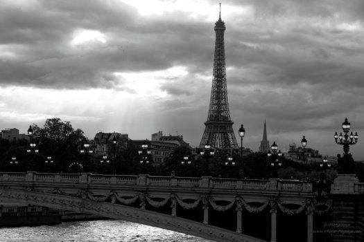 La Tour Eiffel et le Pont Alexandre III à Paris. En arrière plan, des rayons de soleil qui passent à travers les nuages, et, si vous zoomez sur la photo HD, des oiseaux au loin dans le ciel nuageux. Photo en noir & blanc.