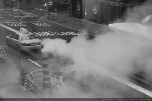 Taxi passant à proximité d'une cheminée de vapeur dans les rues de New York. Photo noir et blanc