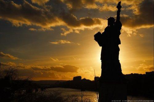 Paris, coucher de soleil au dessus de la seine et statue de la liberté sur l'allée des cygnes.