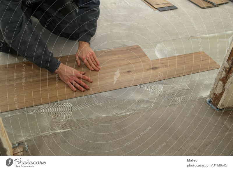 a worker installing new vinyl tile floor a royalty free stock photo from photocase