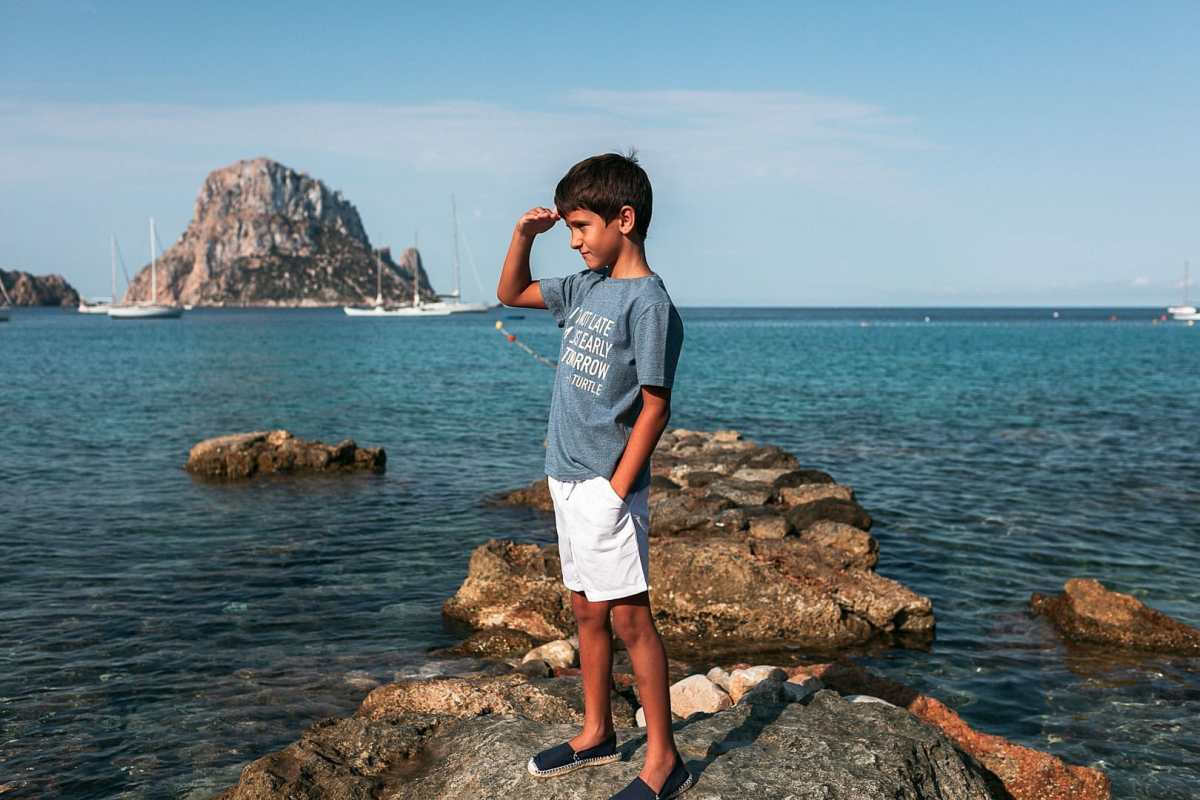 Fotografía de niño posando en las rocas de la cala de Dort por la mañana
