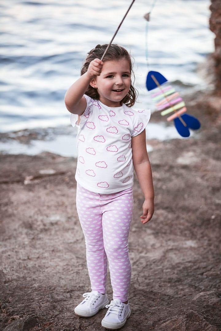 Reportaje fotográfico de ropa infantil con niña vestida con pantalón pitillo y camiseta rosada jugando en embarcadero de Ibiza