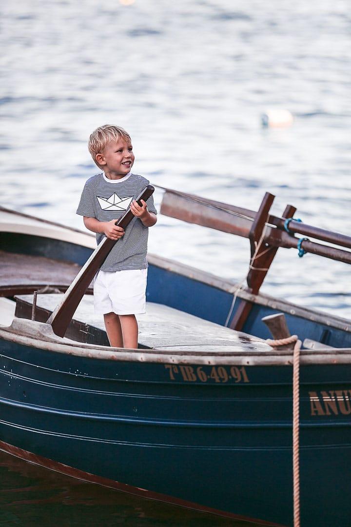 Retrato de un niño sonriente jugando sobre una barca vestido con camiseta rayada de color azul y pantalón blanco en embarcadero de Ibiza