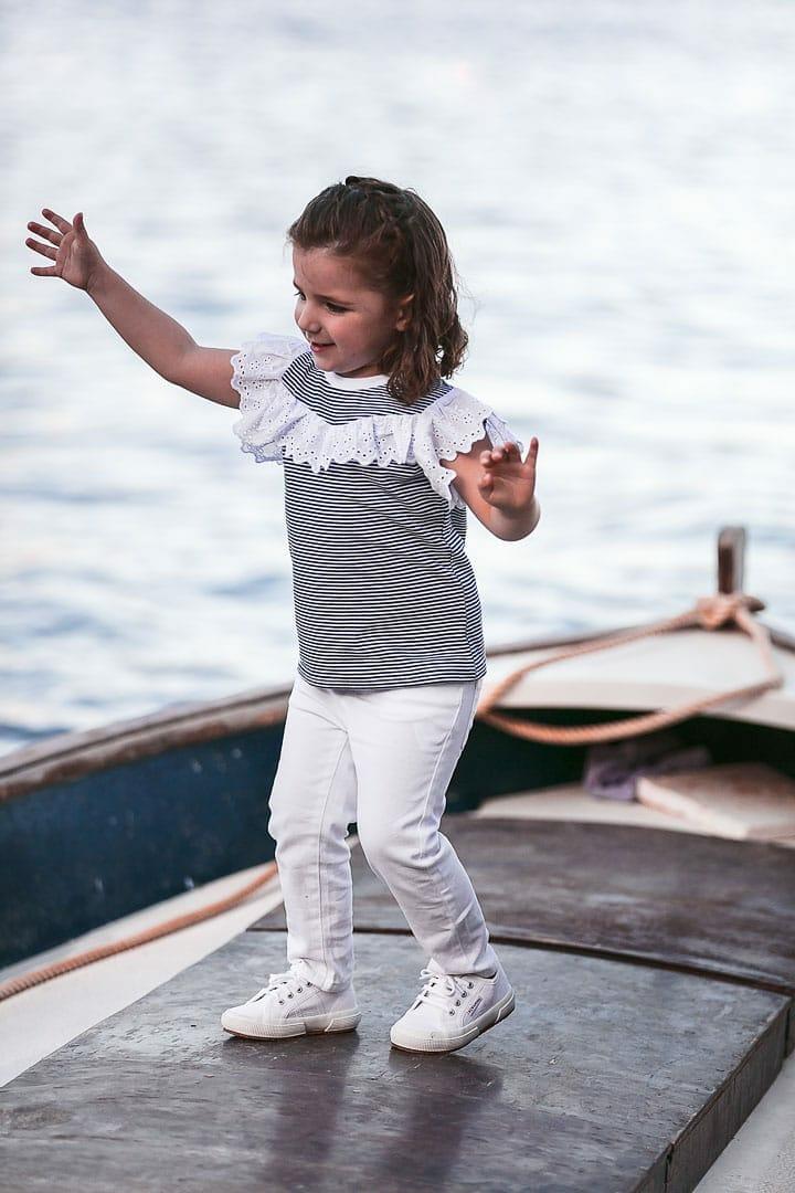 fotografía de una niña sonriente jugando sobre una barca vestida con camiseta rayada de color azul y pantalón blanco en embarcadero de Ibiza